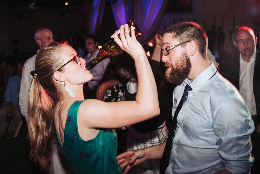 Guests dancing and drinking from bottle.