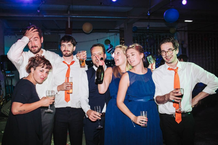 Bridal party pose for photo at the end of the night, drinks in hands.