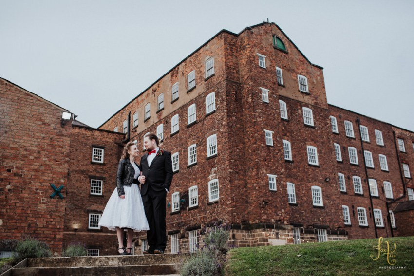 West Mill wedding photography, Derby. Industrial venue with rockabilly bride and groom stood in foreground of mill venue.