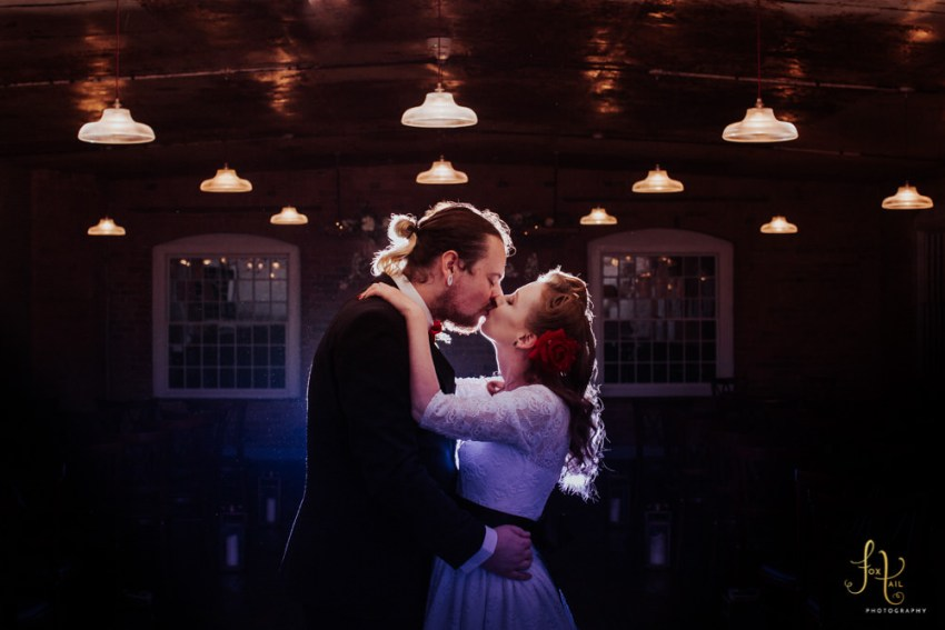 Creative West Mill wedding photography Derby. Rockerbilly couple kiss in industrial venue setting.