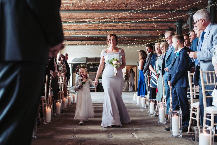 Bridesmaid in grey dress walks down the isle at the Arches with flower girl.
