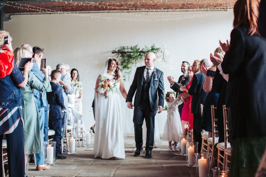 Bride and groom walk up the isle at Yorkshire industrial wedding venue, the Arches.