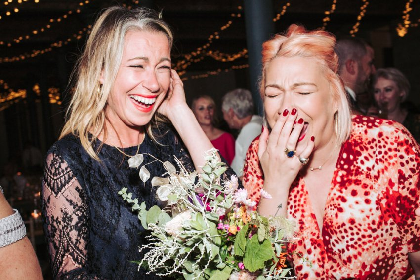 Ladies laughing after one of them has caught the brides bouquet.