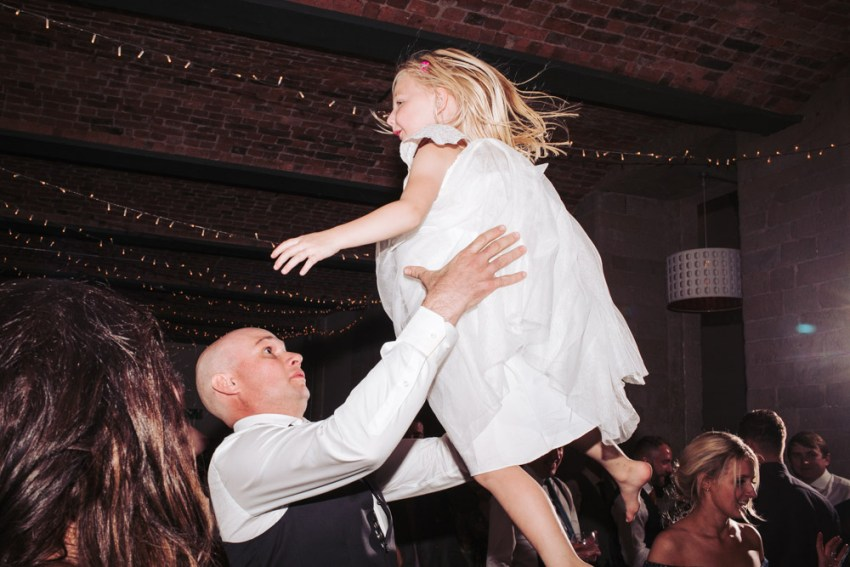 Groom throws the flower girl in the air.