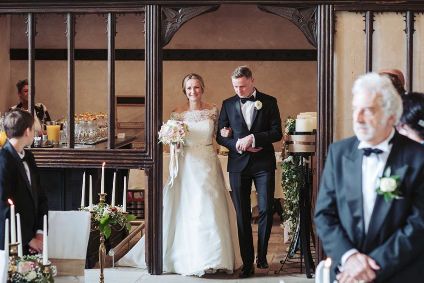 Brides brother, in a tuxedo, walks his sister down the isle wearing a lace dress at Barden Tower Priest House.