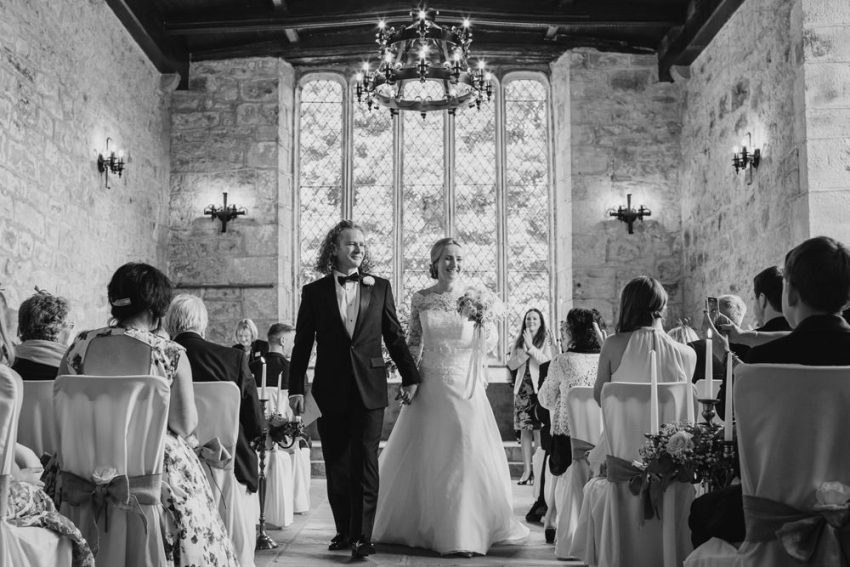 Bride and groom exit at Barden Tower Priest House wedding. Bolton Abbey estate in Yorkshire.