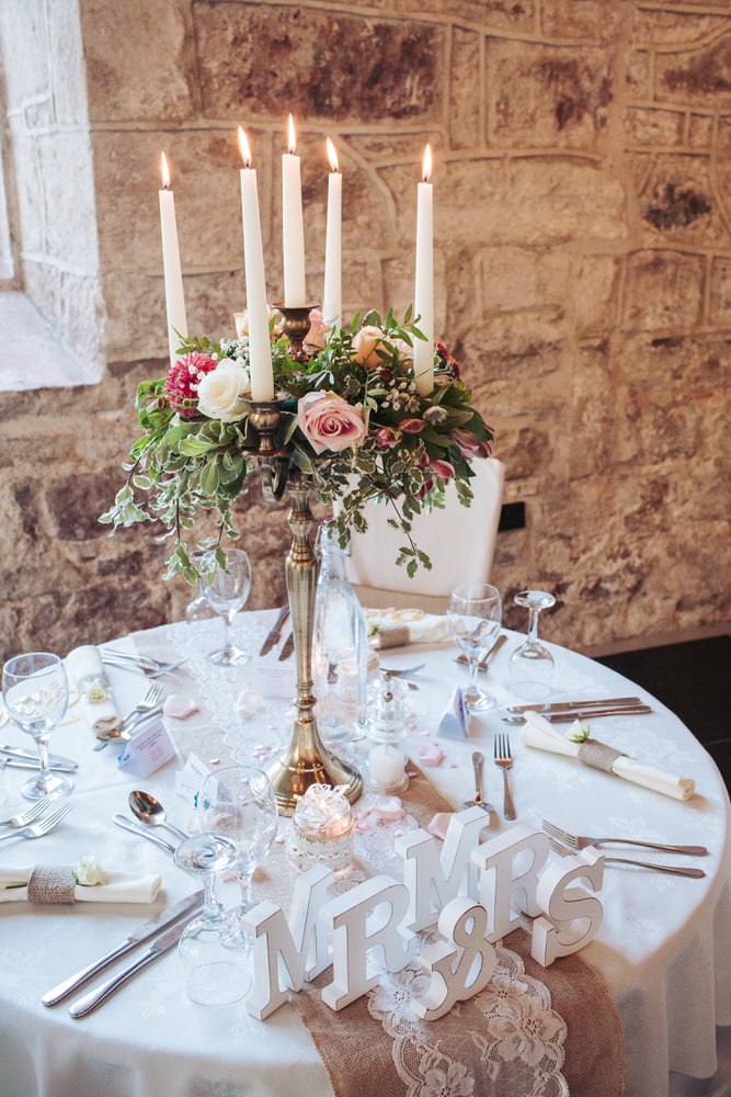 Detail shot of wedding table with rose covered candelabra and lace table runner.