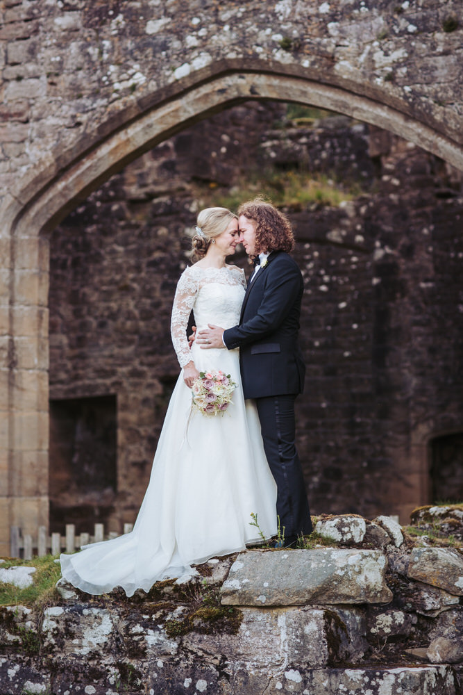 Barden Tower wedding photographer, Priest House, Yorkshire. Bride and groom lace dress and black tuxedo.
