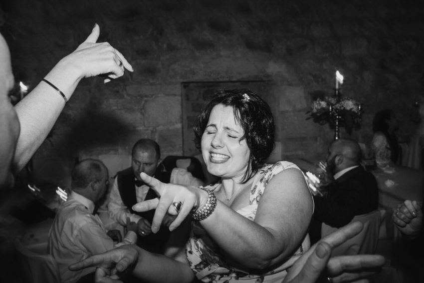 Wedding guest dancing with hands pointing.