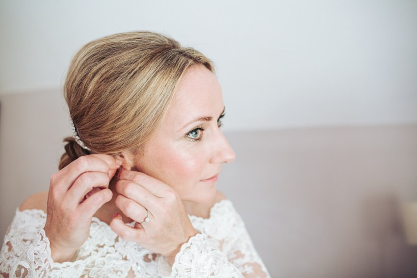 Bride fastening earrings in place, wearing lace wedding dress.