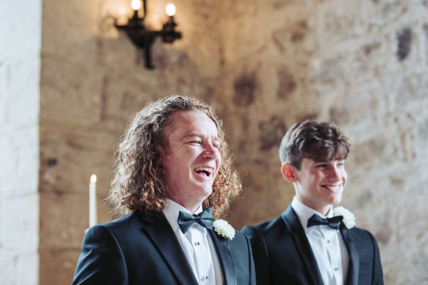 Groom in tuxedo smiles while awaiting his bride.