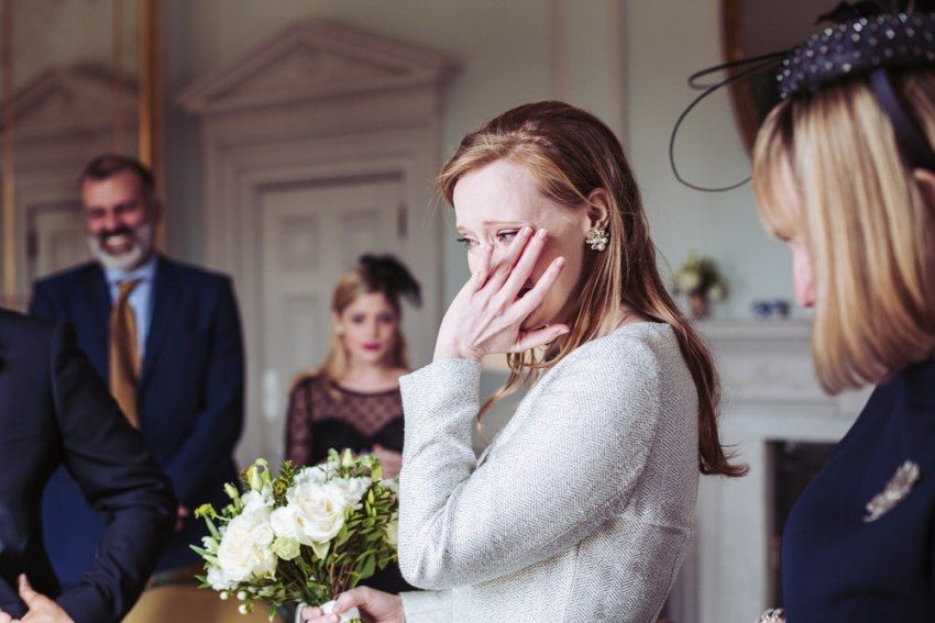 Bride wipes away tear.