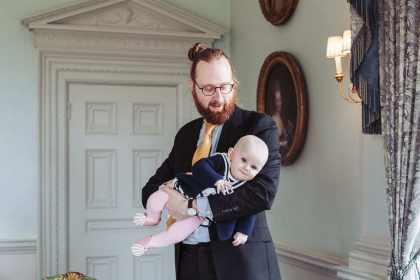 Brother of the bride rocks his baby.