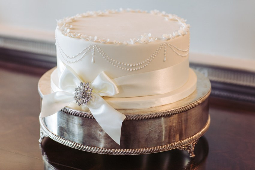 Single tier wedding cake with ribbon and broach decoration.
