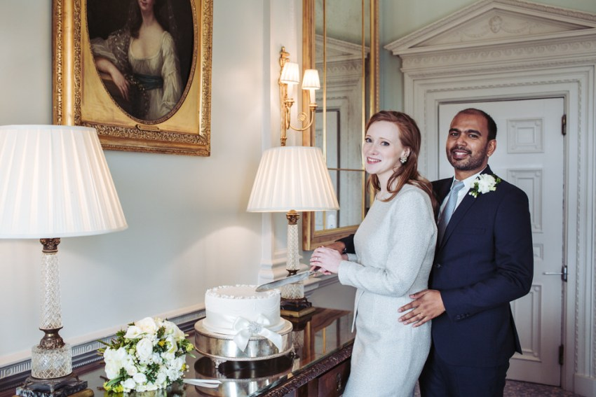 Bride and groom cut the cake at Cliveden House.