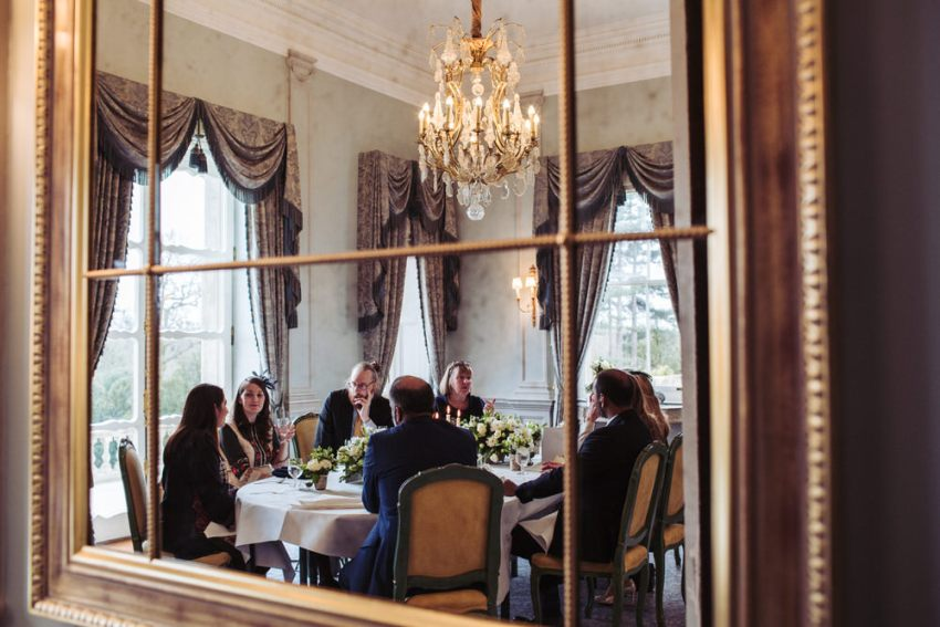Guests seated for the wedding breakfast reflected in mirror, at Cliveden House.