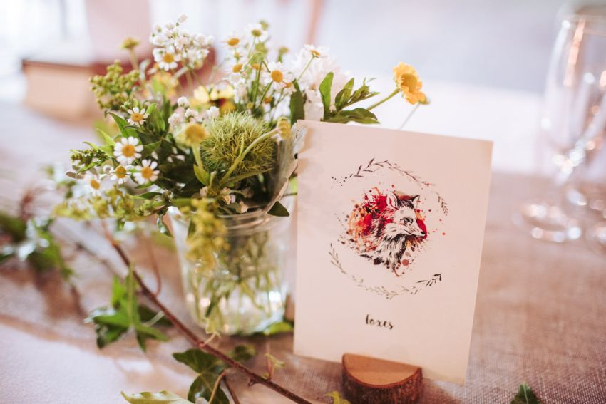 Fox design wedding table card with jar of flowers.
