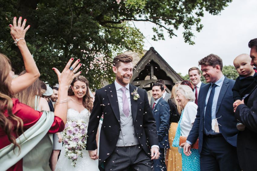 Bride and groom exit church with guests throwing confetti.