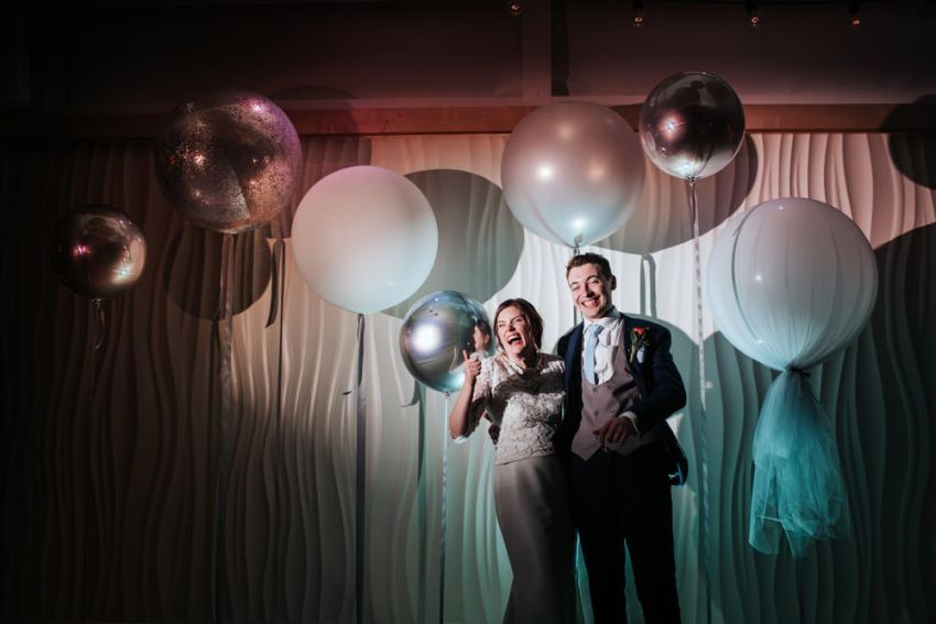 Biscuit Factory wedding photographer, Newcastle. Bride and groom smiling among large balloons.