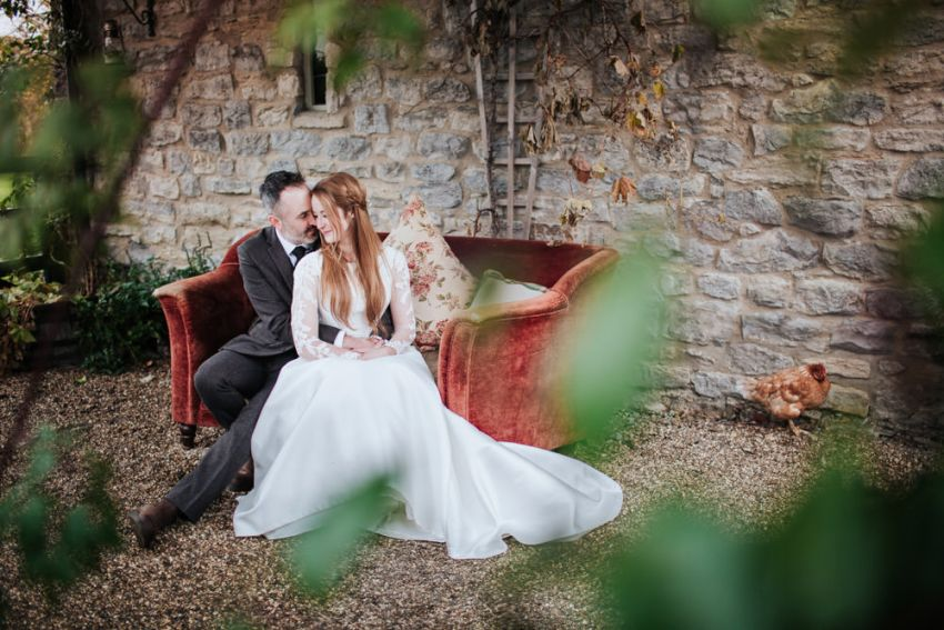 Star Inn Harome wedding photography. Bride and groom sat on outdoor sofa.