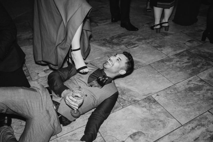 Man lying on dance floor, smiling up at woman who has her foot rested on his chest.