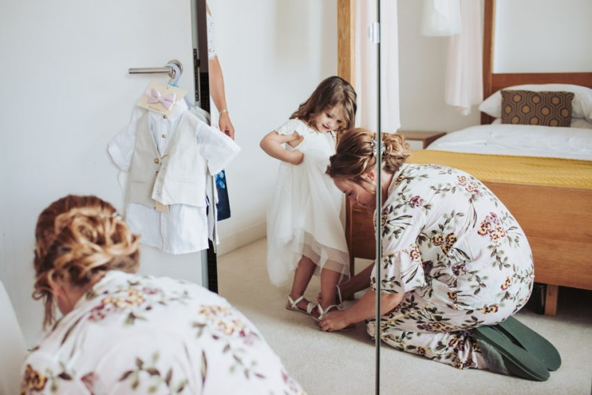 Bride in pyjamas helps flower girl into her shoes.