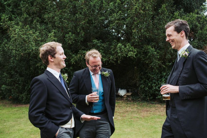 Three wedding guests in suits laughing.
