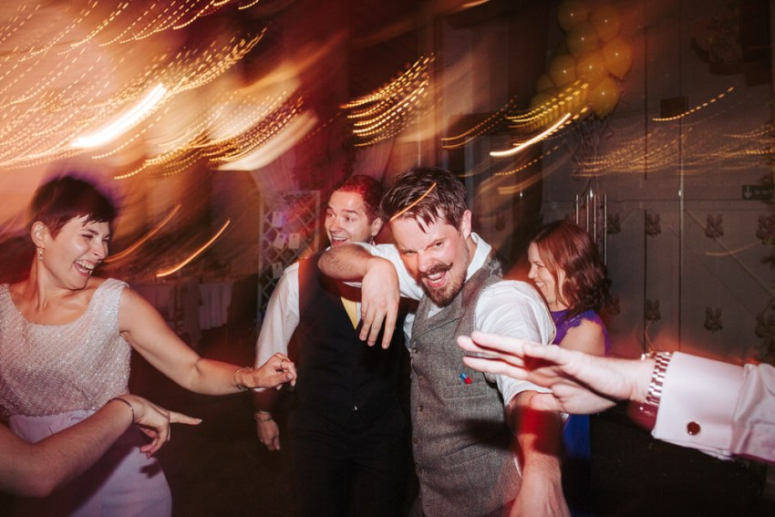 Groom enthusiastically dancing with guests.