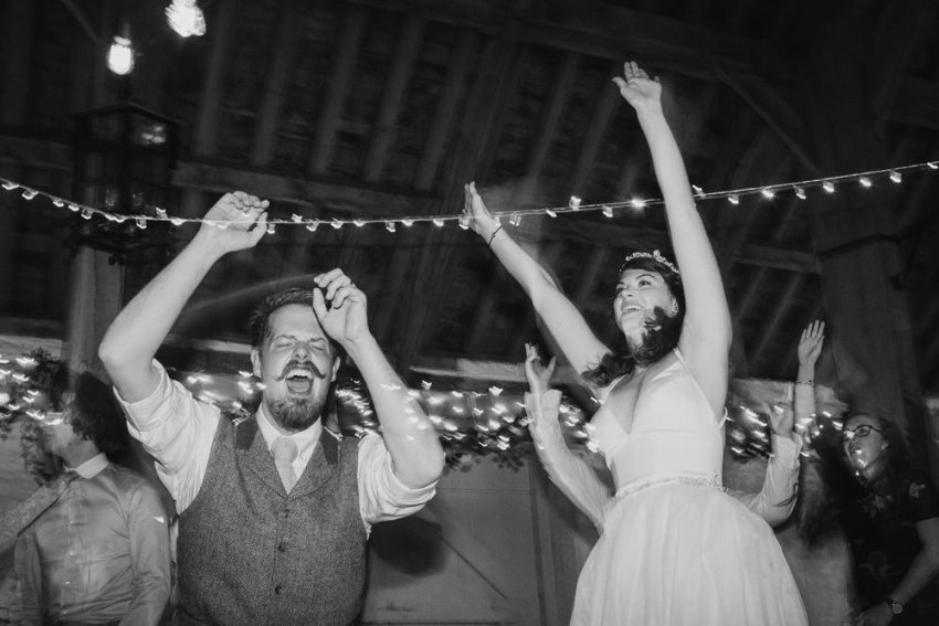 Bride and groom jump, dance and sing in barn venue.