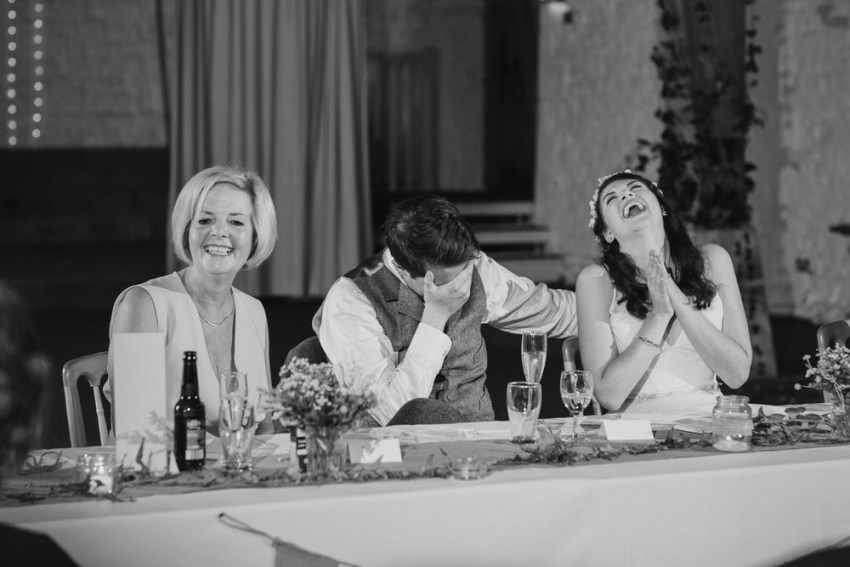 Groom covers his hand over his face out of embarrassment during speeches.