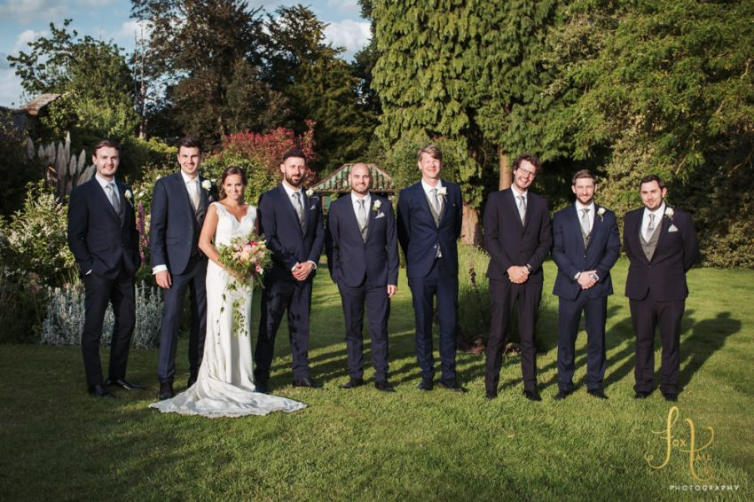 Bride, groom and groomsmen stood together in the gardens.