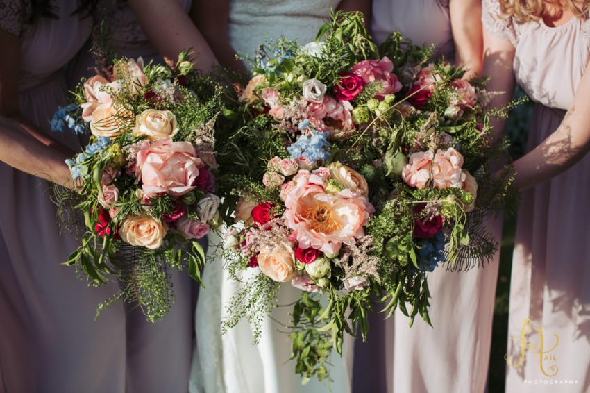 Bride and bridesmaids bouquets by Blue Florist. A mix of cottage garden florals with peach peony's and roses, with red roses and blue delphiniums.