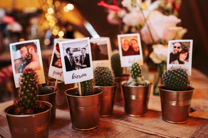 Small cactus plants in tin pots, with miniature Polaroid photos of the guests and table place cards.