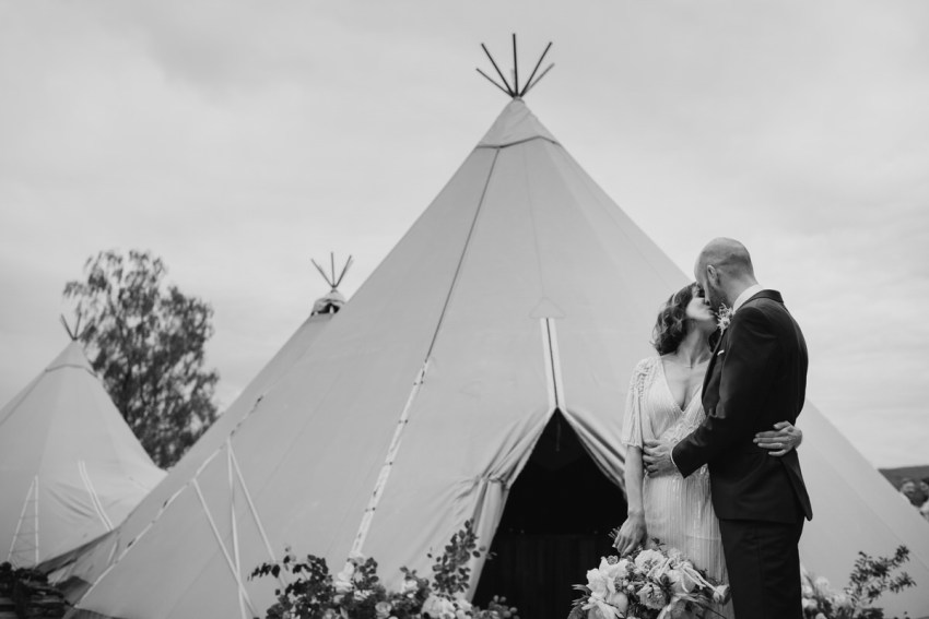 Bride and groom kiss in front of the tipi.