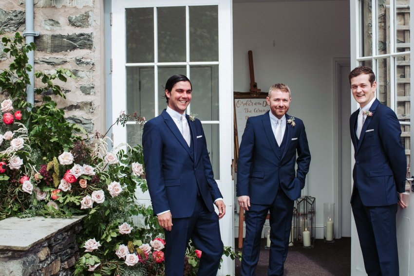 The groomsmen welcome guests to the coach house.
