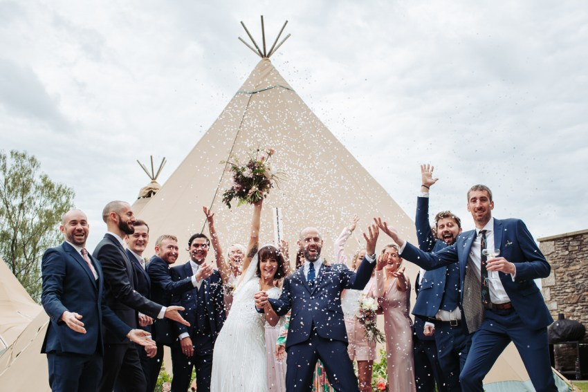 Silverholme Manor wedding photography in the Lake District. Bridal party throw confetti in front of a tipi backdrop.