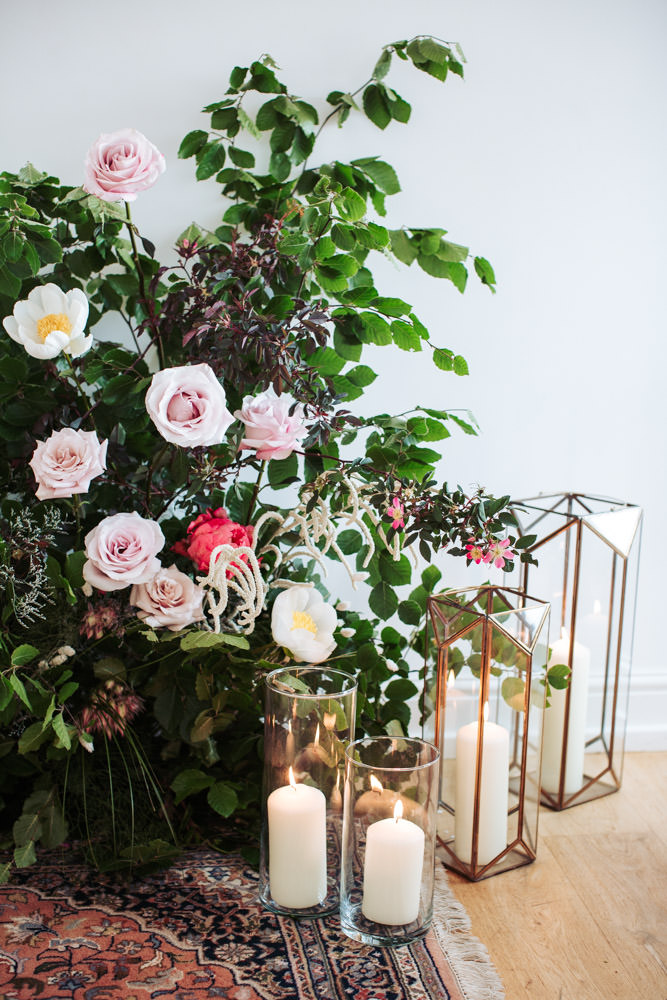 Floral display of dusky pink roses, white and pink peonies and beech foliage.