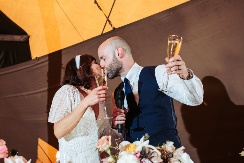 Bride and groom hold champaign glasses in the air while kissing.