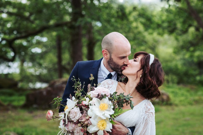 Bride and groom kiss while bride clutches her bouquet of roses and white peonies at a Silverholme Manor wedding.