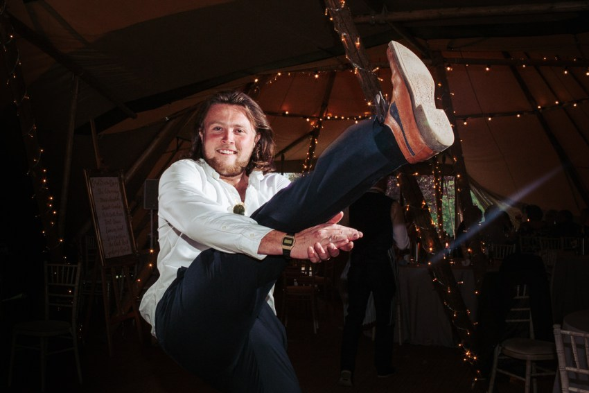 Male guest kicks leg in the air and claps under his leg on the dance floor.