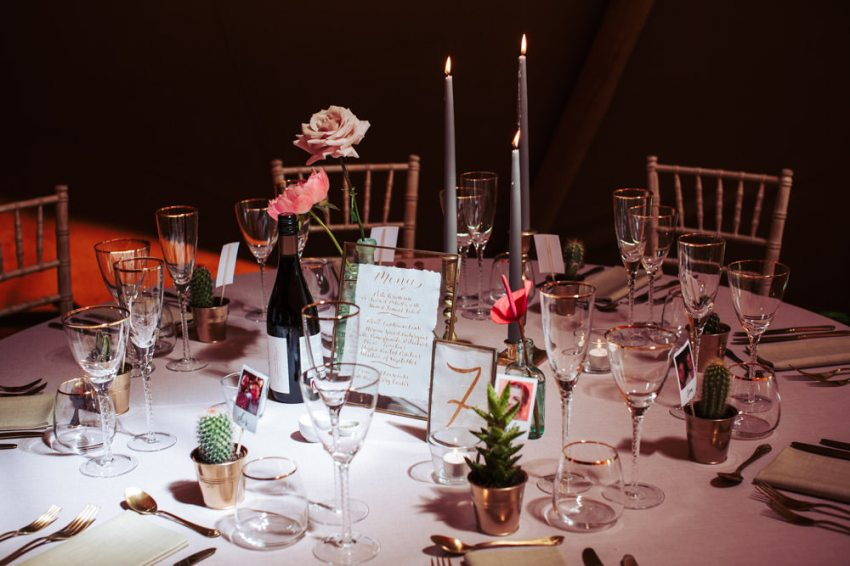 Wedding table with grey candles, glassware and gold cutlery.