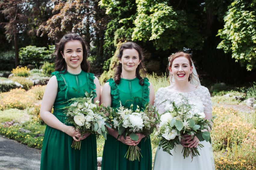 Bride with bridesmaids in deep green dresses, stand together for group portrait in Valley Gardens in Harrogate.