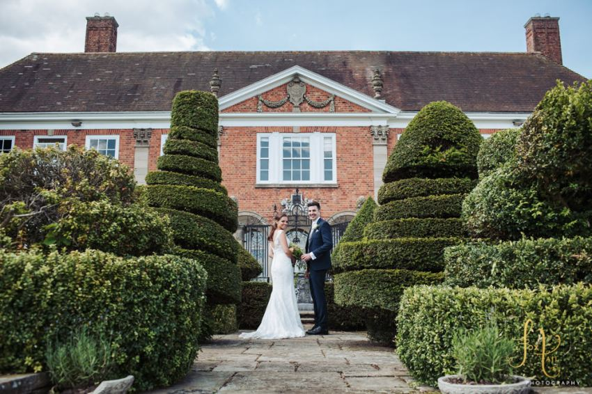 Bride and groom stood in front of Rudge Hall surrounded by topiary hedges.