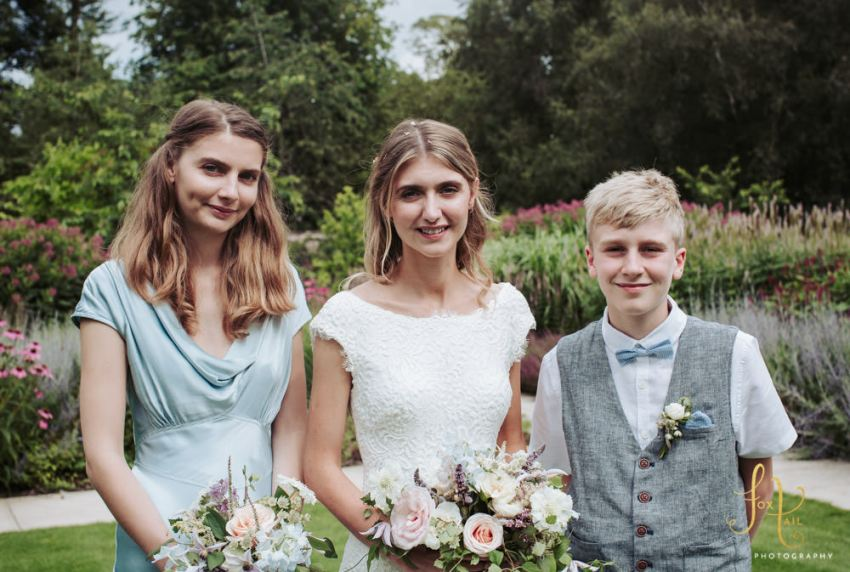 Portrait of bride with bridesmaid and pageboy.