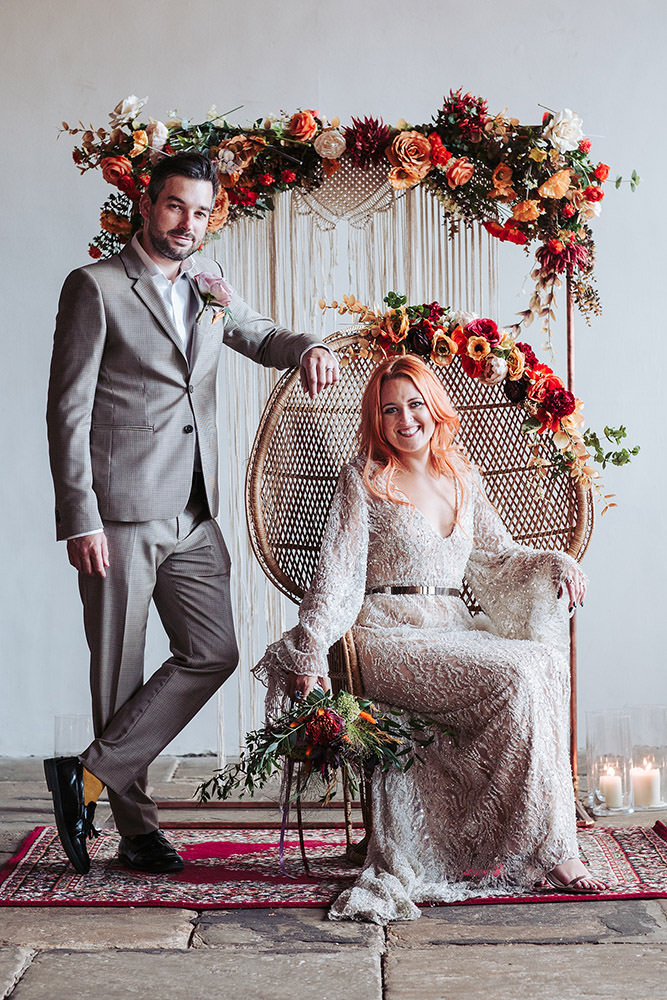 The Arches industrial mill wedding venue near Leeds. Boho styled bride in long sleeved beaded dress, sits on peacock chair. Macrame backdrop adorned with with orange flowers. Groom stands next to the seated bride with arm resting on the chair.