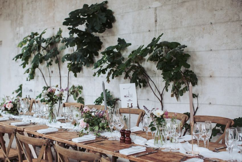 Fig House wedding photography at Middleton Lodge. Trestle table decorated with flowers by wall with fig trees.