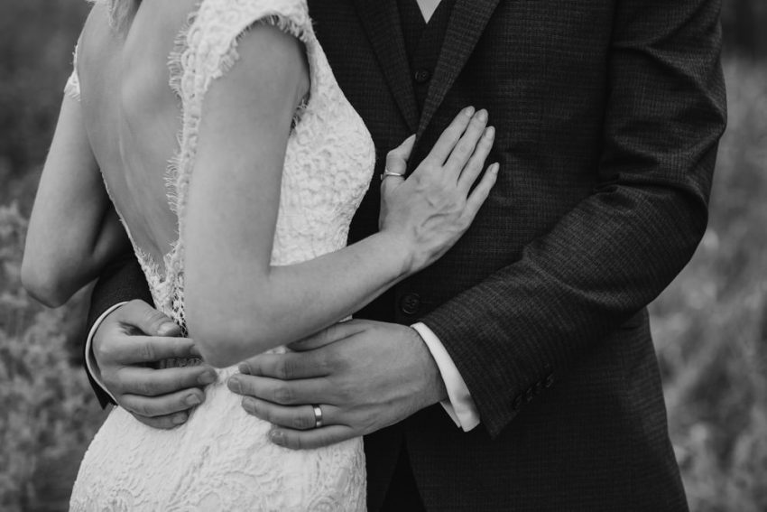 Close up of bride and grooms arms and hands wrapped around each other.