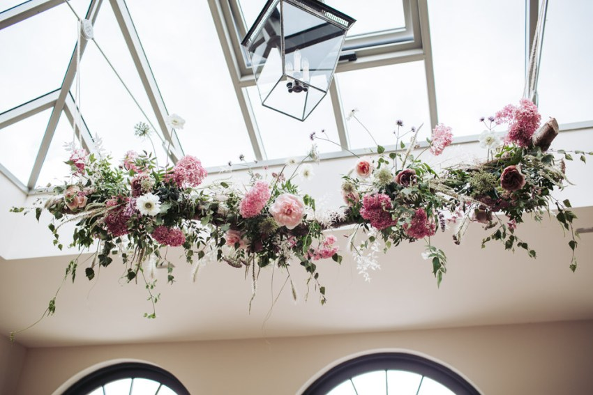 Romantic pink and white floral display hangs from a ceiling.