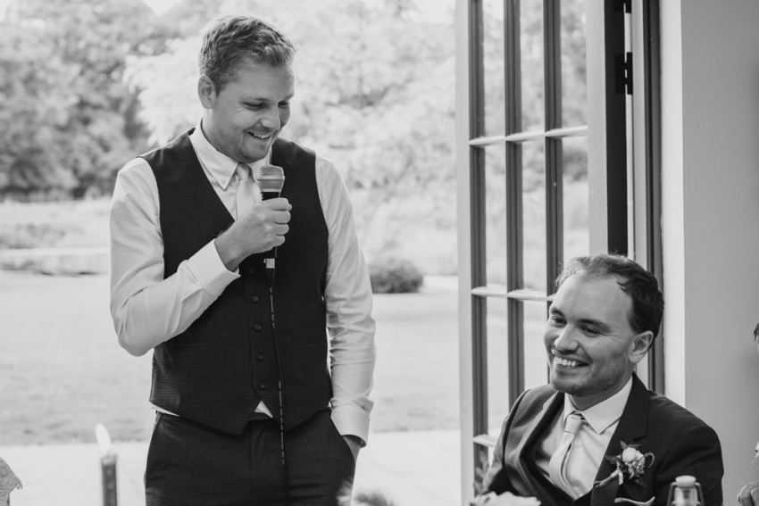 The best man gives his wedding speech as the groom smiles.