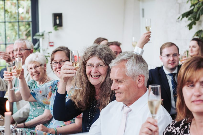Guests raise their champagne glasses for a toast during the wedding speeches.
